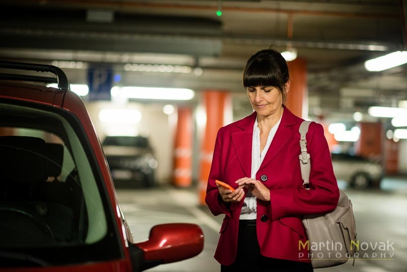 Senior business woman with phone at car