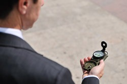 Senior business man looking at compass