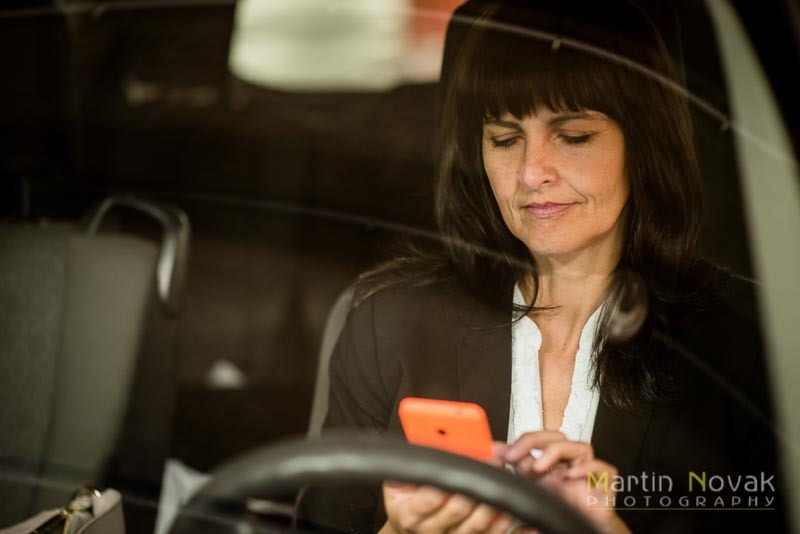 Mature business woman looking to phone in car