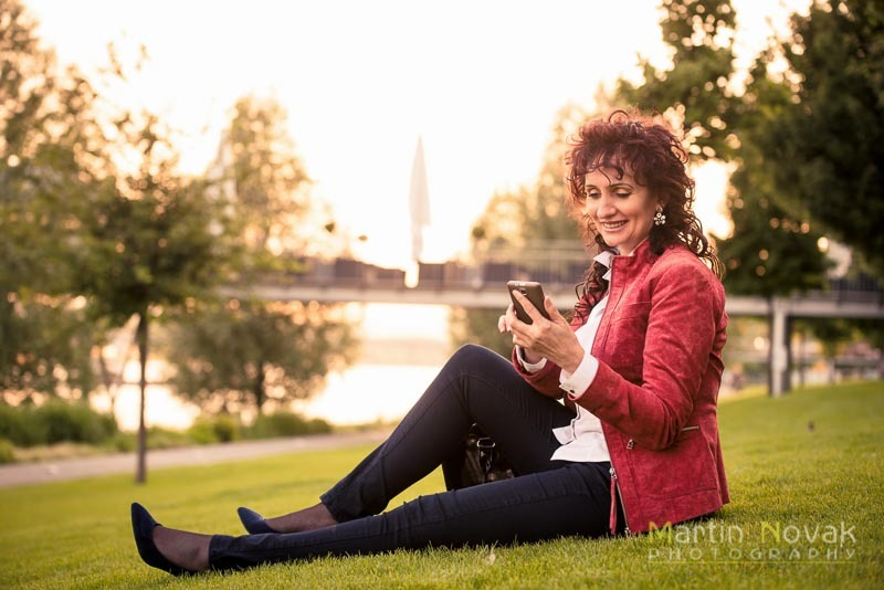 Relax - mature woman with phone sitting in grass
